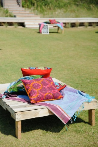 wooden sitting platform for wedding guest covered in wraps and pillows from kenya