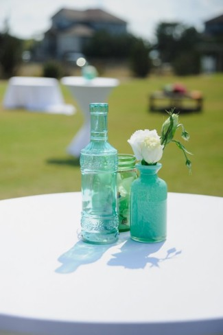 mismatched green glass vases for wedding reception cocktail table center piece