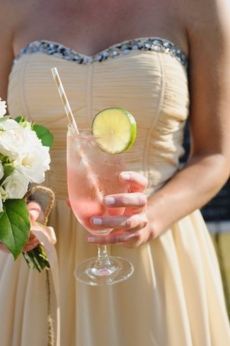 Bridesmaid wearing yellow strapless sweetheart neckline dress holding a cocktail with lime and stipped paper straw