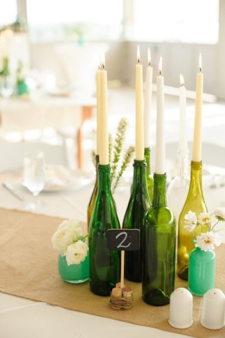 Wine bottles as candle holders with cream and white candles