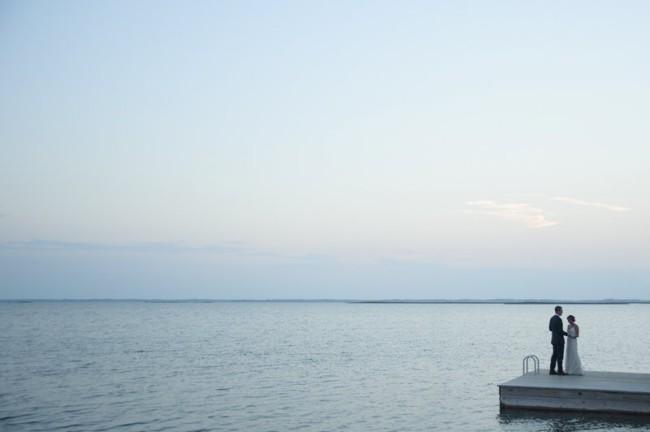 Bride and groom standing on pier at Sanderling Resort at dusk