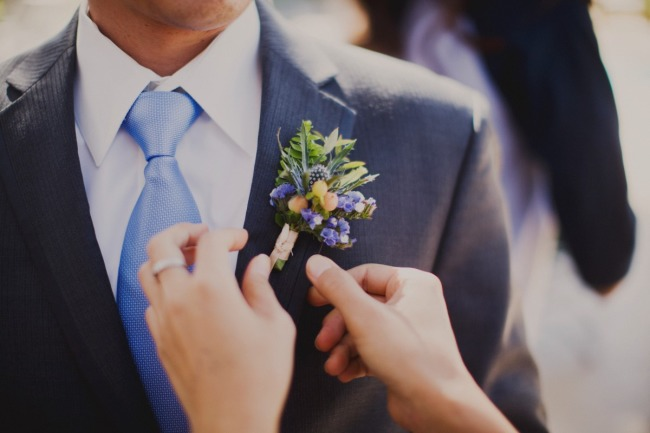 Groom wearing a blue perry winkle tie with a yellow and blue boutonniere
