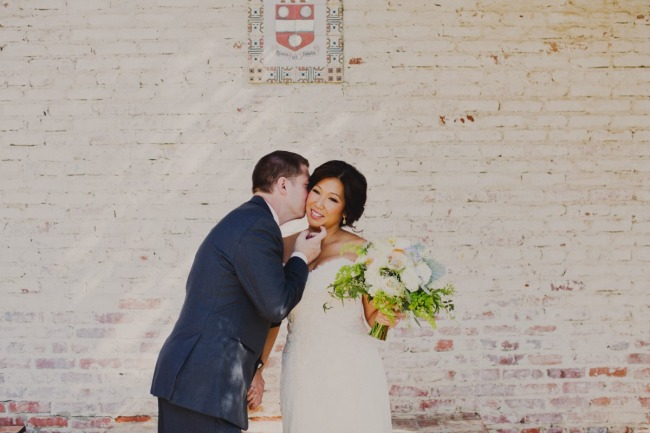 Groom kissing bride on the cheek in front of a white wall