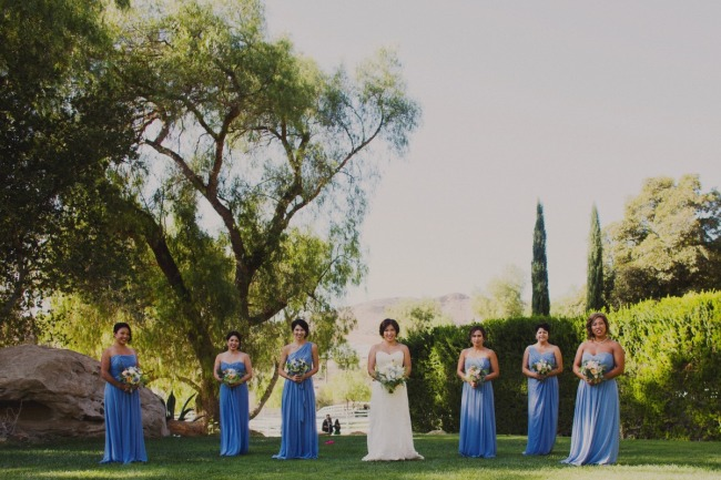 Bride standing with bridesmaids wearing floor length blue dresses