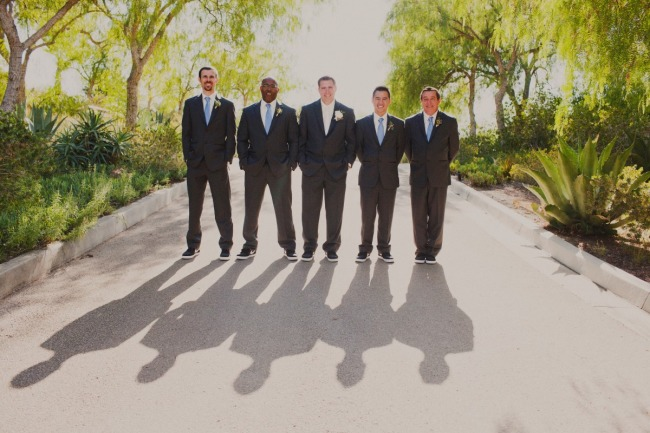 Groom standing with groomsmen wearing blue ties and sneakers