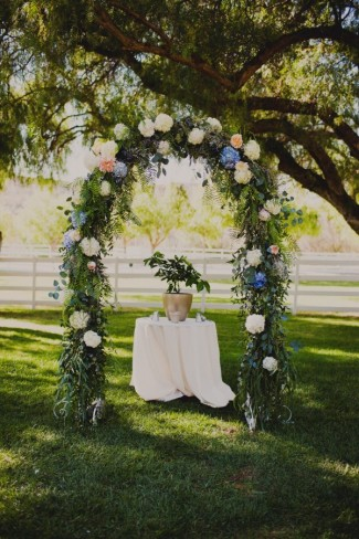 Outdoor wedding ceremony arch way with green foliage and multi color hydrangea