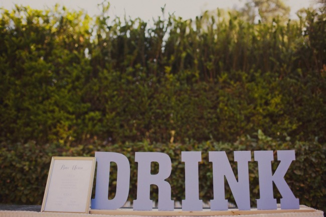 "Wedding reception cocktail hour with large wooden 3d letters spelling ""Drink"""