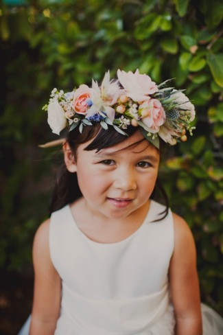 Flower girl wearing a flower crown made with thistle, lisianthus, roses, seeded eucalyptus, and ranunculas