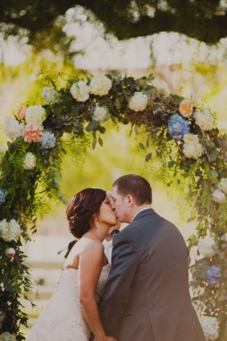 Bride and groom kissing during outdoor wedding ceremony at hummingbird nest ranch
