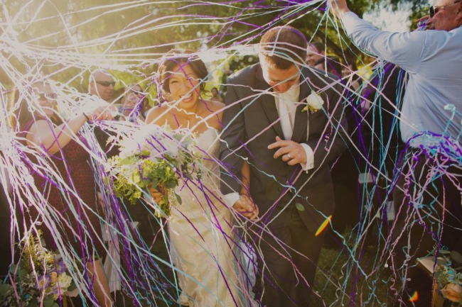 Bride and groom walking down the aisle with guests throwing streamers at them