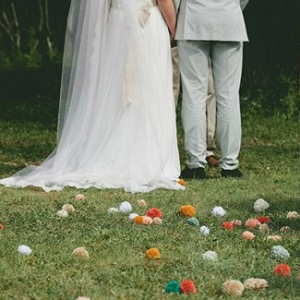 Bride-and-groom-at-altar-with-pom-pom-decor-lining-the-ground-and-hanging-in-trees