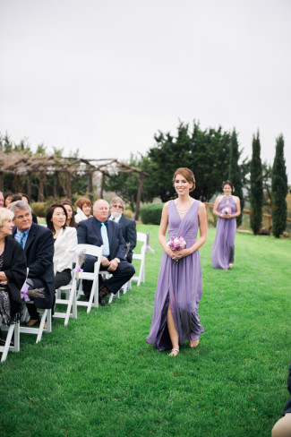 Bridesmaids waking down aisle in long flowy lavender gown