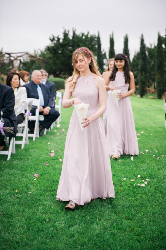Flower maidens walking down aisle at Rancho Mirando wearing light pinky purple gowns