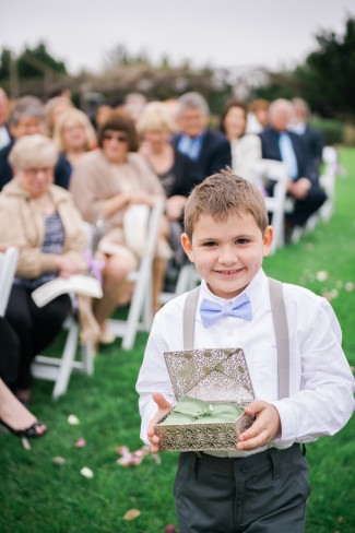 Ring bearer walking down air in lavender colored tie
