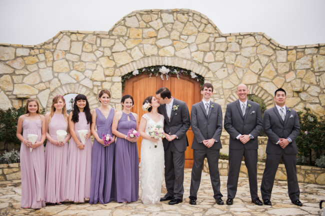 Bride and groom kissing with bridesmaids in purple and groomsmen in grey standing beside them at Rancho Mirando