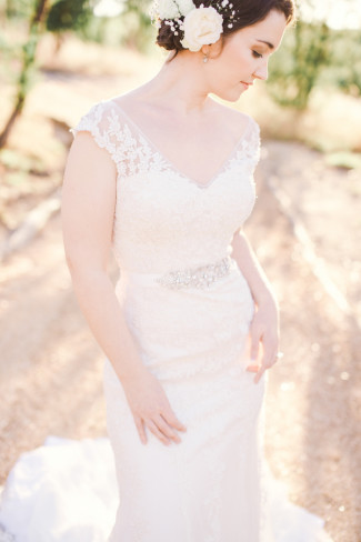 Bridal shoot of bride wearing Maggie sottero gown and roses and baby's breath in her hair