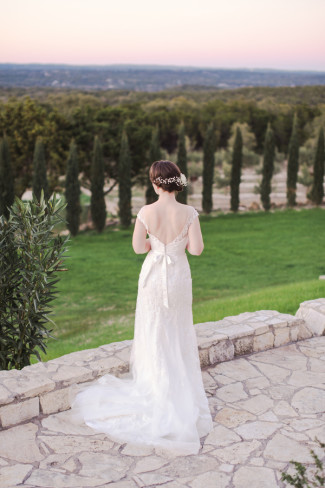 Bride standing on plateau in fit to flare gown and flowers in her hair at Rancho Mirando venue
