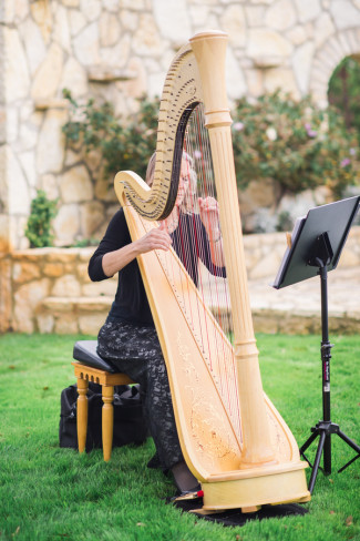 Harpist playing during outdoor wedding ceremony at Rancho Mirando