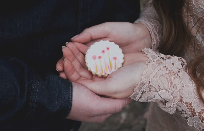 Couple holding a floral cookie created by Turquoise & Pink for rustic engagement shoot