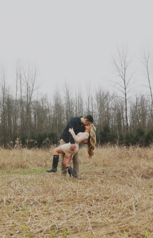 Engaged couple kissing in a field for rustic engagement shoot captured by Jess H. Photography