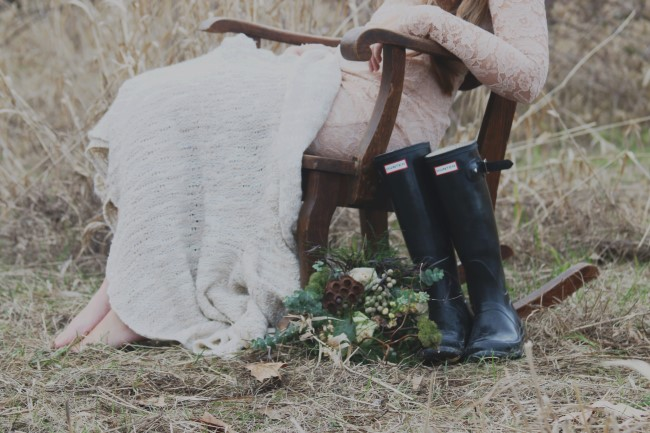Bride sitting in rocking chair with rustic flowers by Korissa and black gum boots