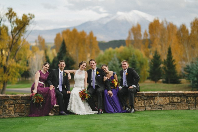 bridal party sit on stone wall with Colorado mountains in background