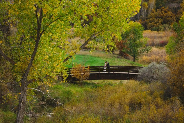 Bride and groom on wooden bridge at Aspen Glen
