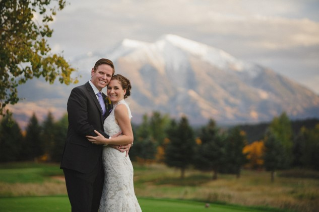 Newlyweds embrace with mountain view background