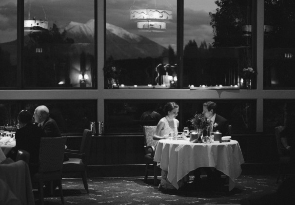 black and white of newlyweds at dinner table for two
