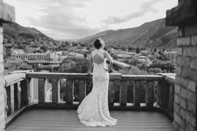 black and white photo bride standing on stone balcony at Aspen Glen