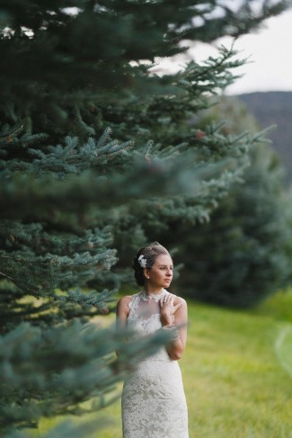 bride posing behind fir tree