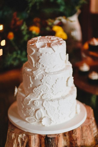 three tier all white wedding cake on wood stump