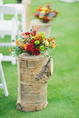 Daisies, zinnias, and buttercup wildflowers on tree stump aisle marker