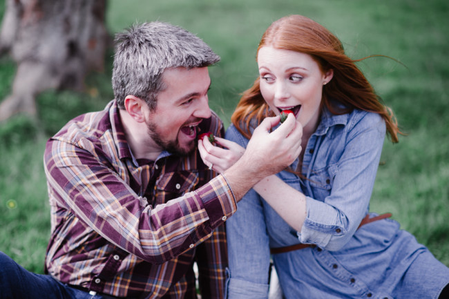 Couple feeding each other berries for outdoor picnic engagement shoot