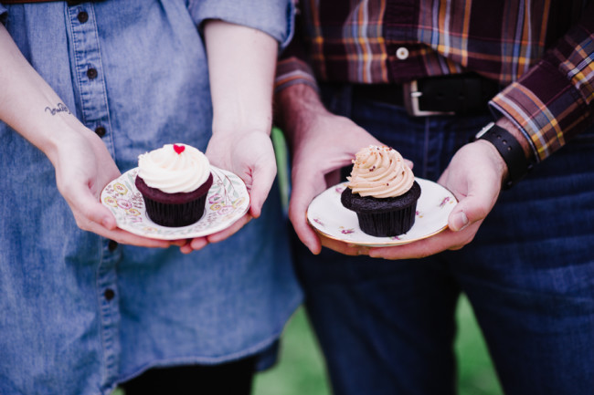 Couple holding china plates with Cupcakes for engagement shoot created by Trophy Cupcakes