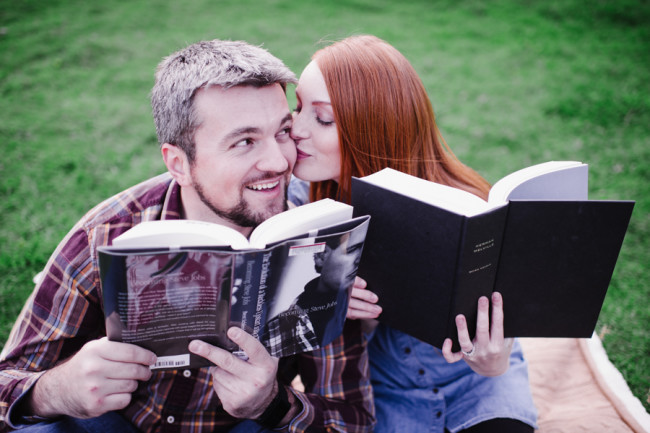 Engagement couple sitting on a picnic blanket reading books outside