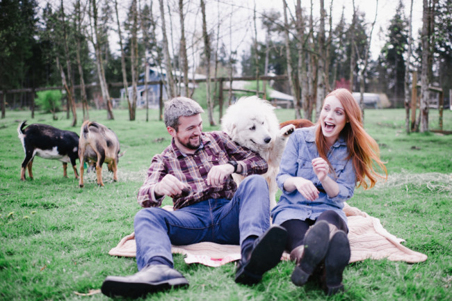 Dog trying to jump on couples lap during outdoor engagement shoot picnic