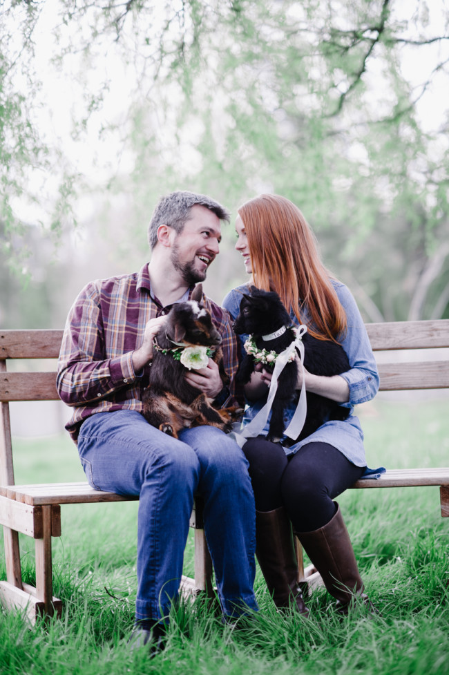 Couple sitting on bench holding baby goats at Left Foot Farm for engagement shoot