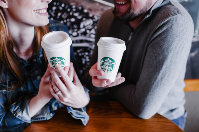 Couple holding Starbucks paper cups for engagement shoot while bride to be shows off her ring