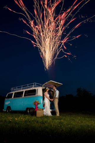 Bride and groom standing in front of blue van watching fireworks by Pyrotex
