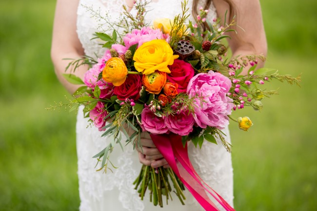 Bride holding a bright colored bouquet created by Fleurs de France