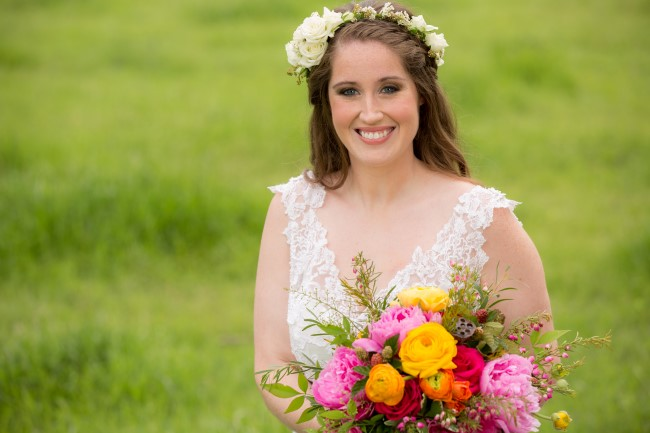 Bride wearing a white floral crown and holding a bright colored bouquet created by Fleurs de France
