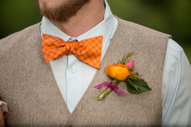 Groom wearing an orange tie and orange boutoniere created by Fleurs de France