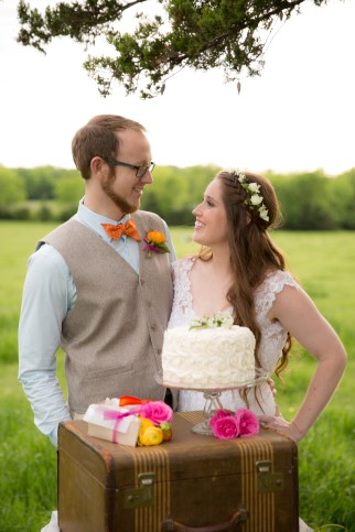 Bride and groom standing in front of one tier white wedding cake with rosettes