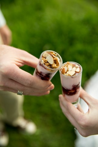 Bride and groom holding yogurt parfaits by Uncle Willie's Pies and Catering