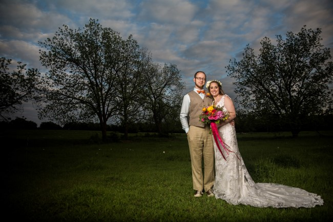 bride and groom standing in a field at dusk captured by Justin Yoder Studios