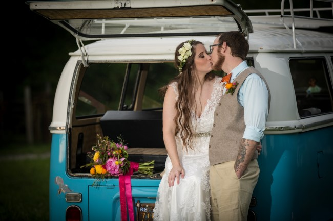 Bride and kissing in front of a blue westafilia van rented from The Photobus DFW