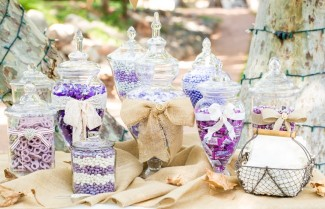 apothecary-jars-filled-with-purple-and-white-candy-and-with-white-and-burlaps-bows