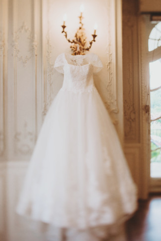 Sottero & Midgley gown hanging from a wall sconce