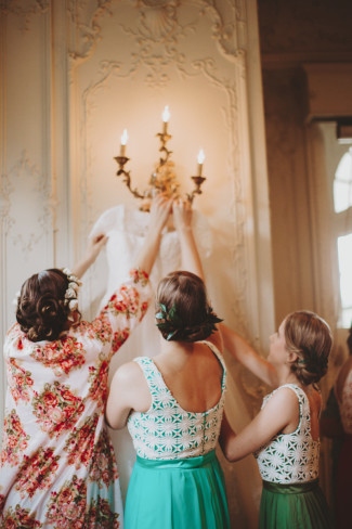 bridesmaids pulling down a Sottero & Midgley gown from the wall sconce